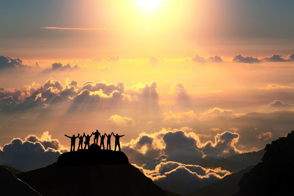 45235301 - on the top of the world together. a group of people stands on a hill over the beautiful cloudscape.